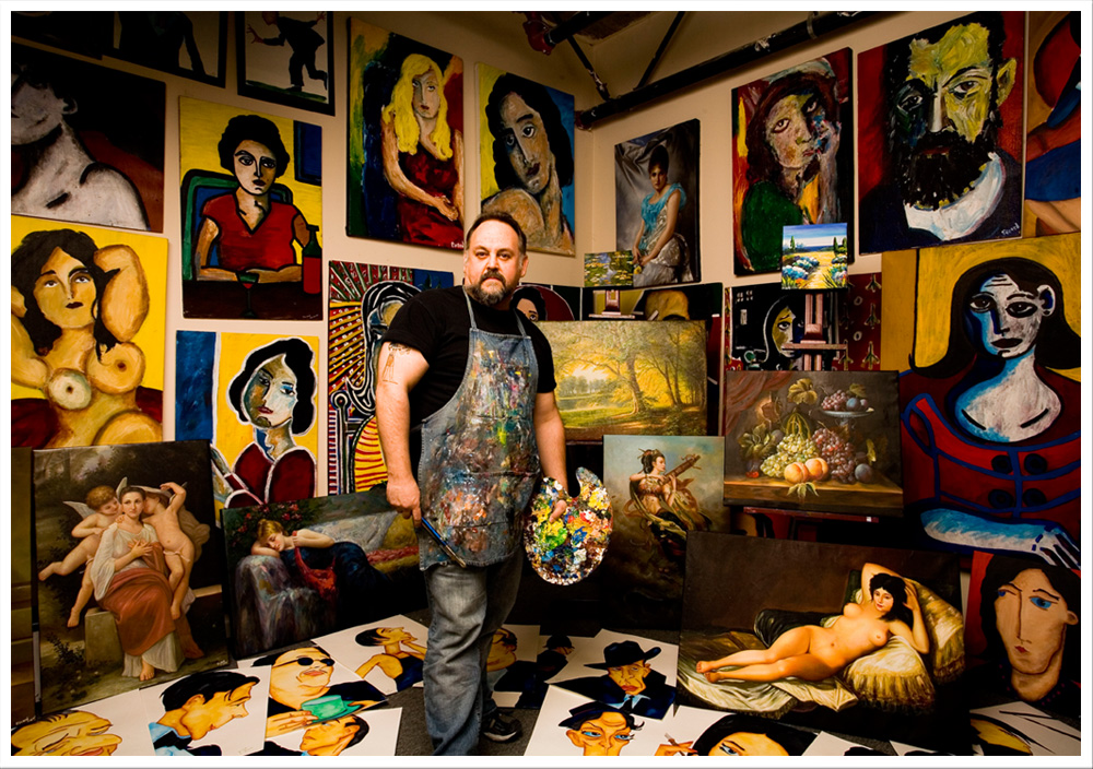 James amongst a handful of his paintings. Photo courtesy of www.jamespicard.com.
