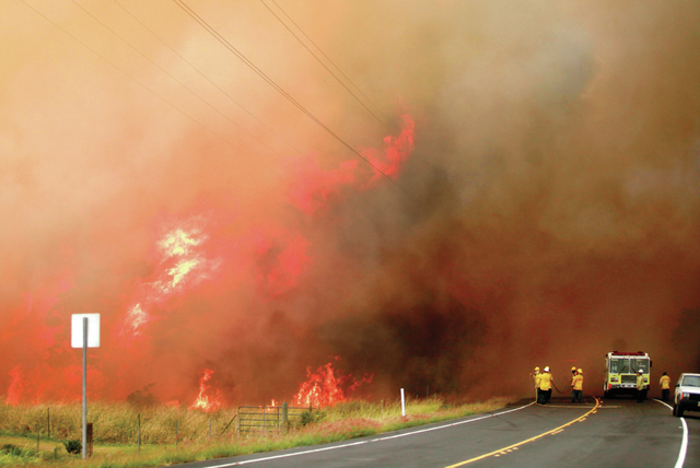 """Fire fighters work to control a brush fire near mile marker 50 on Hawaii Belt Road (Highway 11) in Kau Tuesday afternoon."" Credit: Hollyn Johnson/Tribune-Herald"