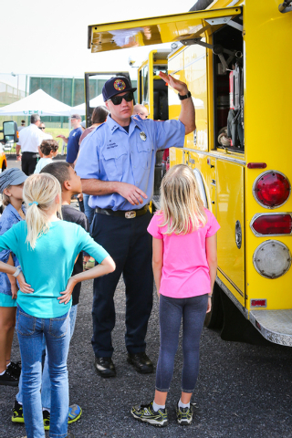 """Firefighter Paul Higgins gives keiki a tour of a fire truck during the day of fire preparedness at Waikoloa Dryland Safety Park on Saturday."" Credit - West Hawaii Today"