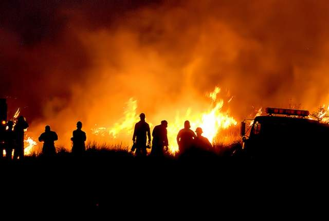 "Above: ""Firefighters watch a brush fire burn in Kona in July 2013."" Credit: West Hawaii Today"
