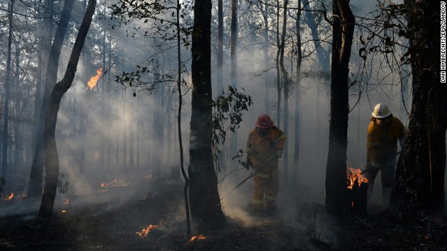 Above: New South Wales Rural Fire Service crews mop up an area after stopping a fire in Bilpin in the Blue Mountains of Australia on October 23.