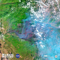 "Above: ""A recent image from the Landsat 8 satellite in the vicinity of Yosemite National Park, California, during the Rim Fire (August 31). Started on August 17, the Rim Fire had burned over 219,000 acres by August 31 (an area nearly 15 times the size of Manhattan Island). Image is false-colored using bands 6, 5, 4 to allow identification of critical vegetation and fuels information that will help firefighters and emergency managers. In the image fire appears bright red, vegetation is green, smoke is blue, clouds are white, and bare ground is tan-colored."""