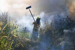 "Above: ""Firefighter Roland Alcantra prevents a fire in Talofofo from spreading by snuffing out the flames. Yesterday, firefighters dealt with several small grass fires in Talofofo and Inarajan. Smoke from an Inarajan fire filled Inarajan Middle School, leading Department of Education officials to close the school early. Sean-Michael Davis/For Pacific Daily News"""