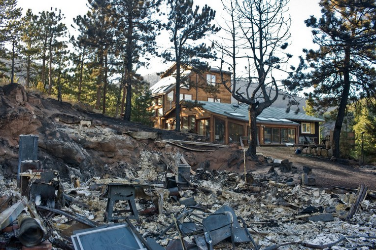 "Above: ""The wreckage of a burned structure sits near a surviving home after the 2010 Fourmile Canyon Fire near Boulder, Colorado. The 7,000 acre fire claimed nearly 170 houses in the first days of the blaze. Several of the houses that were saved had properly prepared their land for the potential of wildfire, including building with fire resistant materials as well as preparing defensible, fuel-minimized spaces in the areas surrounding the structure."" Credit: Matt Slaby/Luceo"