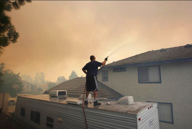 "Above: ""Bert Newman sprays water on his home as a wildfire driven by fierce Santa Ana winds closes in on him in Rancho Cucamonga, California, April 30, 2014. Credit: David McNew/Reuters"""