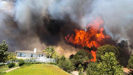 "Above: ""Flames near a house in Carlsbad, Calif., May 14, 2014."" Credit: Daniel Knighton/Getty Images"
