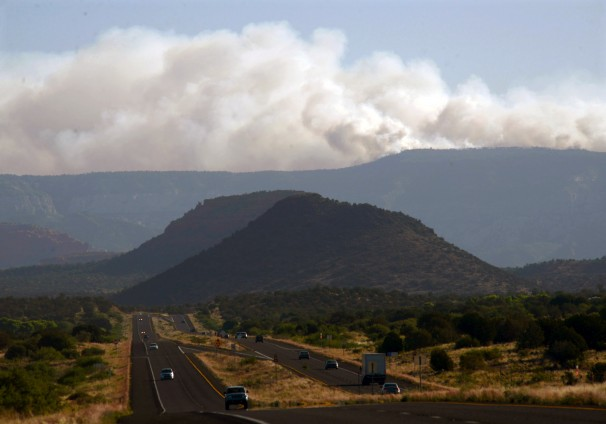 "Above: ""Plumes of smoke from a wildfire rise from Oak Creek Canyon in Sedona, Ariz., as seen from I-89A near Sedona, Ariz.,on May 21, 2014."" Credit: AP Photo/Vyto Starinskas"