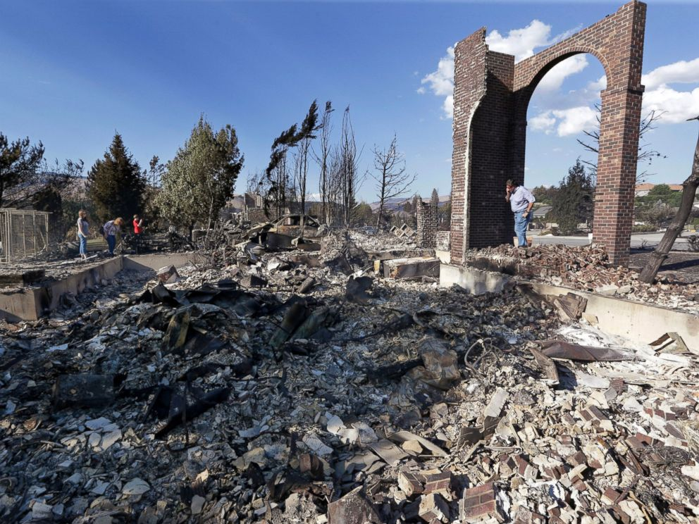 """PHOTO: A man stands in front of the remains of his fire-destroyed home, June 29, 2015, in Wenatchee, Wash."" Credit - Elaine Thompson/AP Photo"