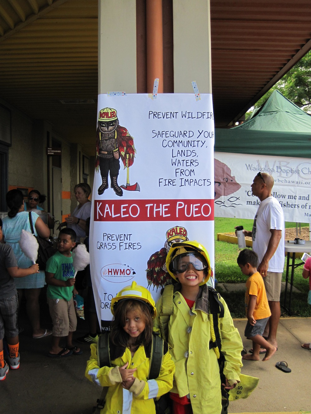 Dressing up in wildland fire gear and posing in front of Kaleo the Pueo (and cotton candy enthusiasts!)