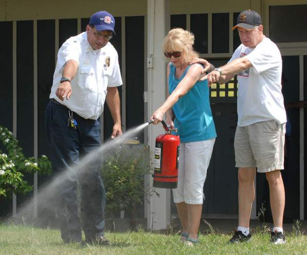 """Fire Battalion Chief Joseph Farias left indicates where to aim the spray to Mary and Dale Watson at a fire extinguisher workshop Saturday at the Waikoloa Stables. Laura Shimabuku/West Hawaii Today"""