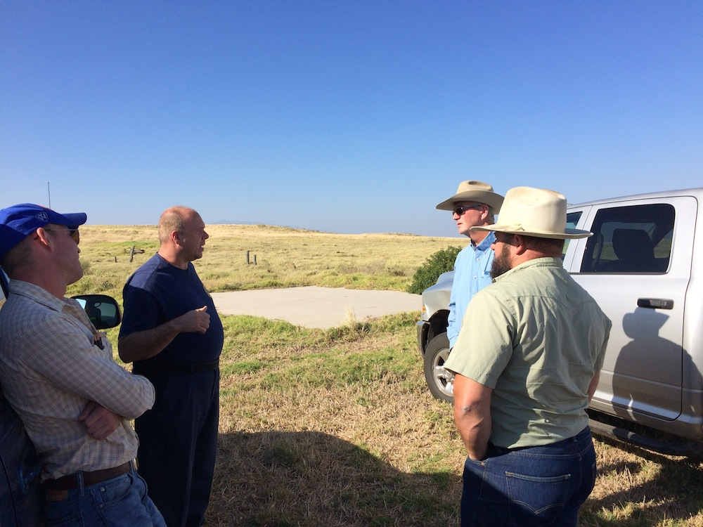 Chief Moller (left) of USAG-FES speaks with Keoki Wood of Parker Ranch (second from right) and HWMO President and UH Grazing Specialist Mark Thorne (right) about logistics for the day.