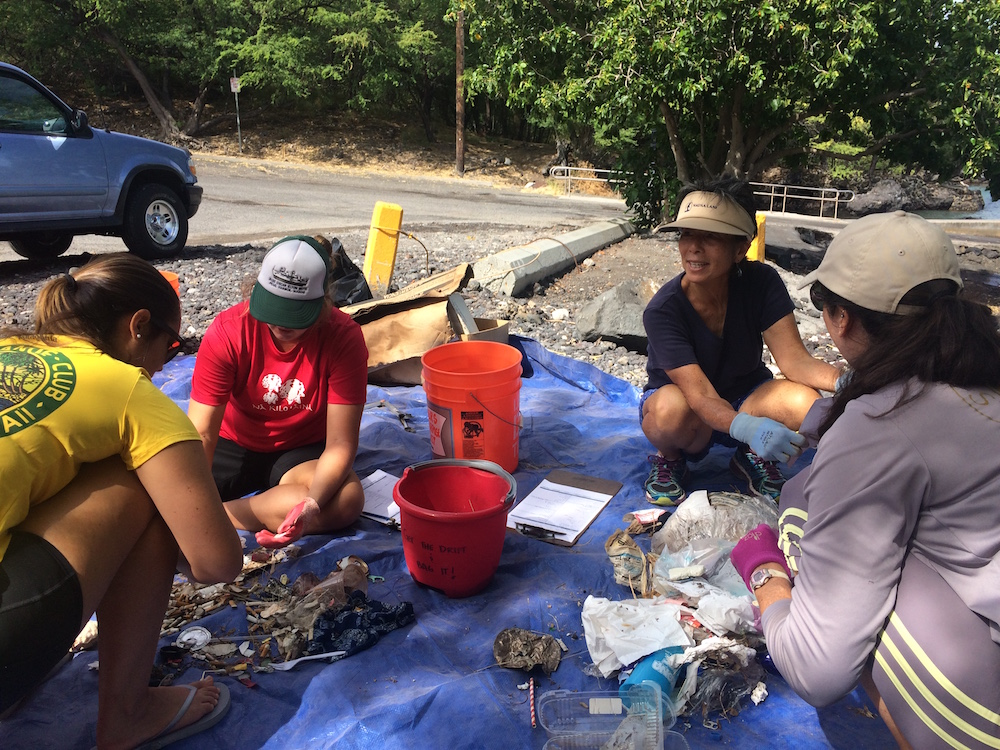 Cynthia Ho (top right) leads the charge to clean and sort debris at Puako Boat Ramp to prevent coral reef pollution and wildfires.