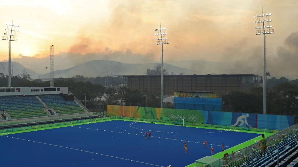 """Athletes from Spain warm up on the pitch as a wildfire burns in the nearby hills of Deodoro before the quarterfinal hockey game against Great Britain on Day 10 of the Rio 2016 Olympic Games, Aug. 15, 2016 in Rio de Janeiro, Brazil."" (Christian Petersen/Getty Images)"