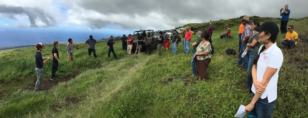 Firefighters share their experiences fighting fires in Kahikinui. Attendees listen in as they survey the land from the mauka edge of the fire. Photo Credit: Clay Trauernicht/PFX