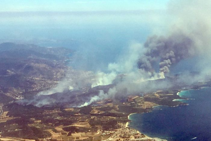"""An aerial view shows plumes of smoke on the outskirts of Bormes-les-Mimosas."" Credit: Nadine Achoui-Lesage/AP"