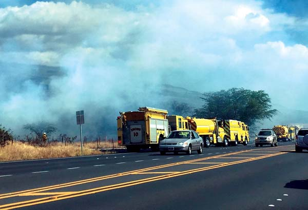 """Maui Fire Department trucks are lined up along Piilani Highway in Kihei on Saturday afternoon while firefighters battle a brush fire mauka of the highway near the Kaonoulu Street intersection."" Credit: The Maui News / Colleen Uechi"