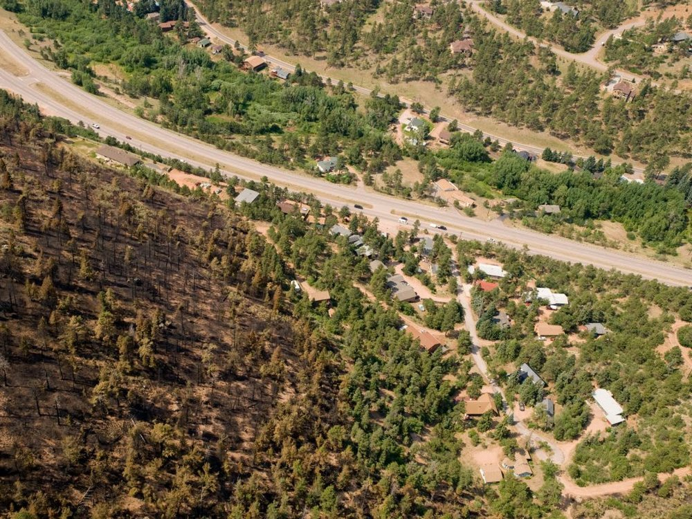 """Where wildfire meets homes, the fire suppression response may protect homes but distort the full cost of insuring the homes from wildfires. Waldo Canyon Fire, Colorado Springs, CO, 2012."" Credit: USFS"