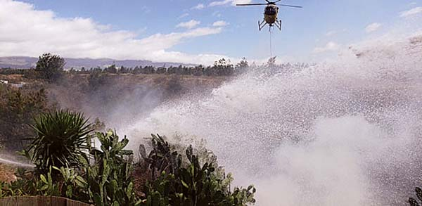 """The Fire Department's Air One helicopter helps battle a fire in a Pukalani gulch Tuesday afternoon."" Credit: Maui Fire Department"