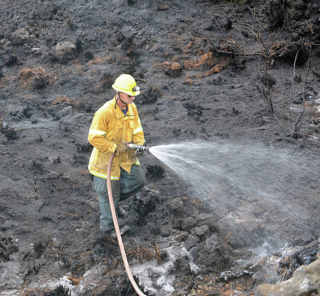 """A Hawaii County firefighter douses a brush fire off Highway 190 near mile marker 18 Friday afternoon."" Laura Ruminski / West Hawaii Today"