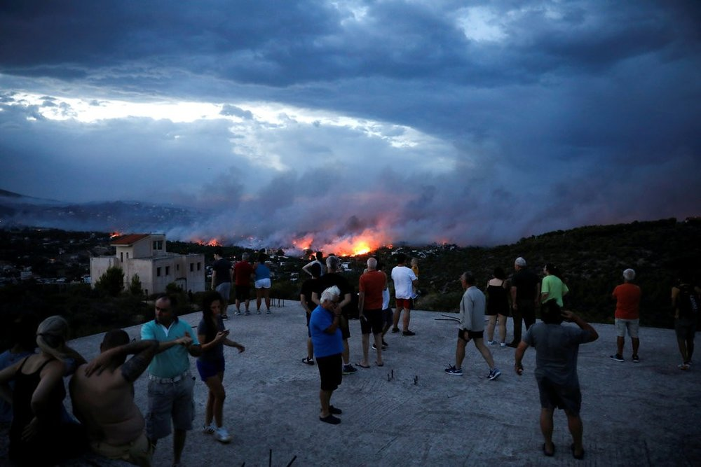 """People watching a wildfire raging on Monday in Rafina, east of Athens."" Credit Alkis Konstantinidis / Reuters"