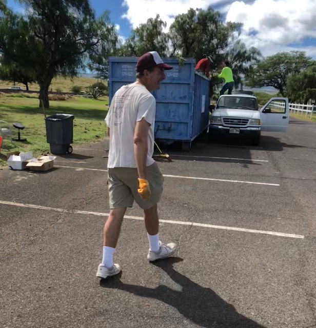 Mark Gordon, Fire Management Action Committee Chair, shares a laugh in front of the roll-out dumpster used for the green waste collection event. Credit: Waikoloa Village Fire Management Action Committee