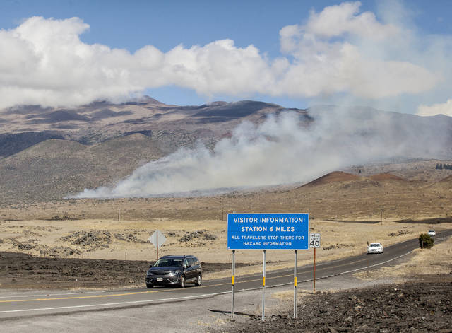 """A brush fire continues to burn off Daniel K. Inouye Highway Wednesday near near the Maunakea Access Road."" (HOLLYN JOHNSON/Tribune-Herald)"