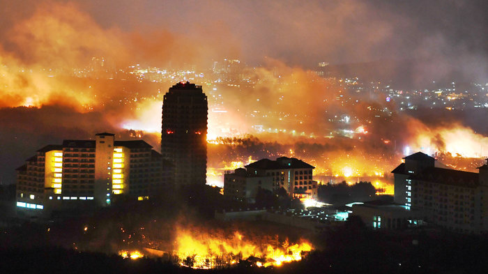 """""""A forest fire is seen raging near buildings in Sokcho, South Korea. South Korea mobilized troops and helicopters to deal with the massive blaze that roared through forests and cities along the eastern coast."""" Credit: Kangwon Ilbo / Getty Images"""