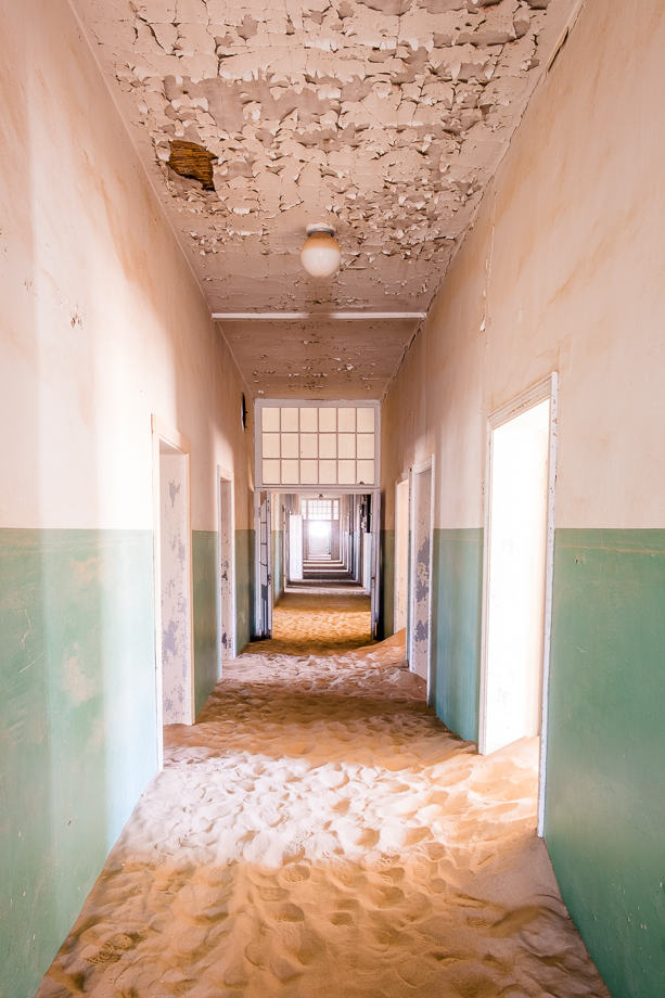 The long hallway of the hospital building, being overtaken by the dunes