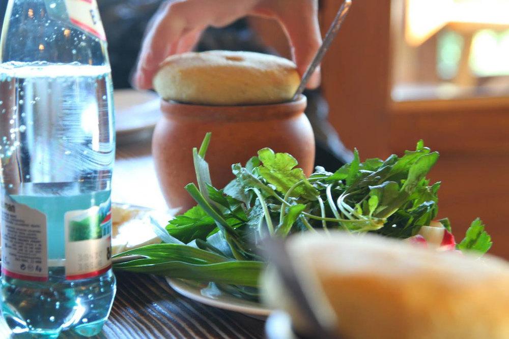 Настоящий грузинский обед: в горшочках мацони, лепешка сверху, ткемали, зелень, красное саперави и боржоми.