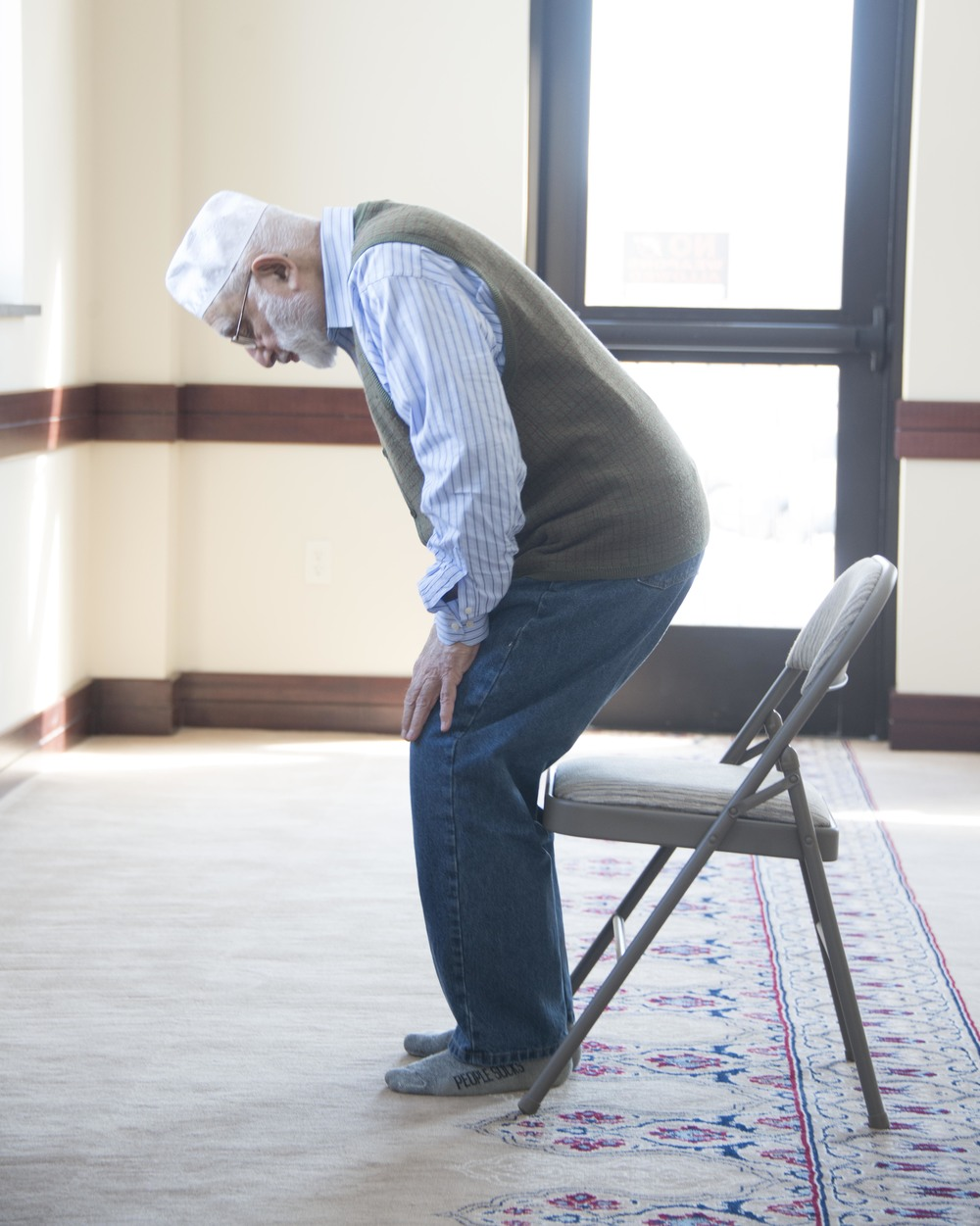 An elderly gentleman offers Namaz