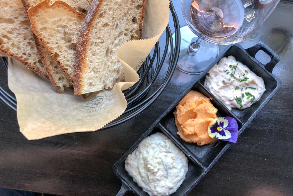 - Next, we enjoyed a fresh basket of Red Bird Bakery bread with a trio of house made spreads (from left to right): artichoke, pimento cheese, and smoked salmon. The appetizer paired beautifully with a crisp sparkling wine. Our choices were Rack & Riddle's Sparkling Rose and Blanc de Blanc - yum!
