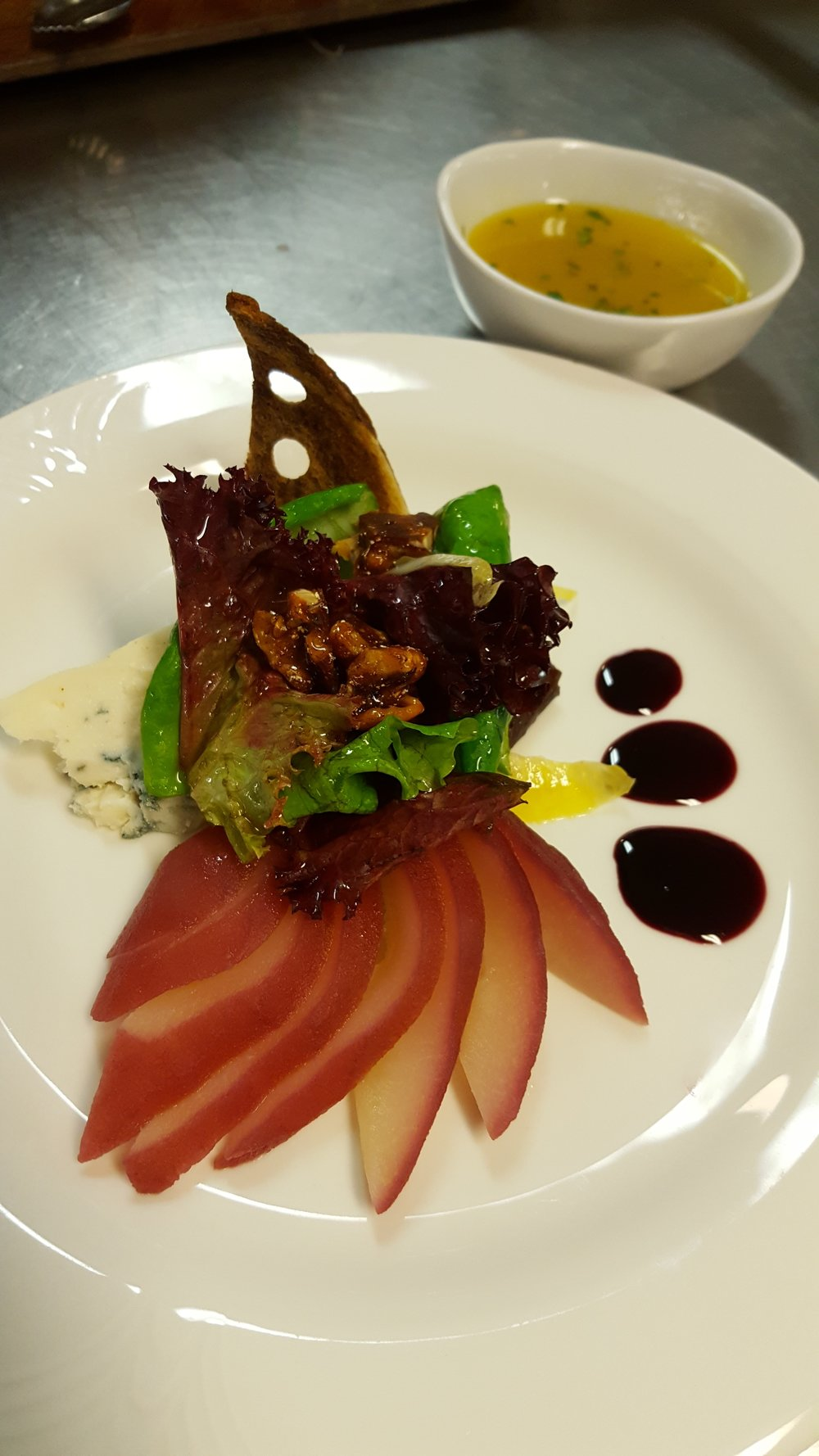Salad: Port Wine Poached Pear, Tossed Field Greens. Served with Danish Blue Cheese, Praline Pecans, and Balsamic Vinaigrette