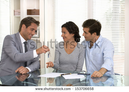 stock-photo-real-estate-agent-giving-keys-to-new-property-owners-153706658.jpg