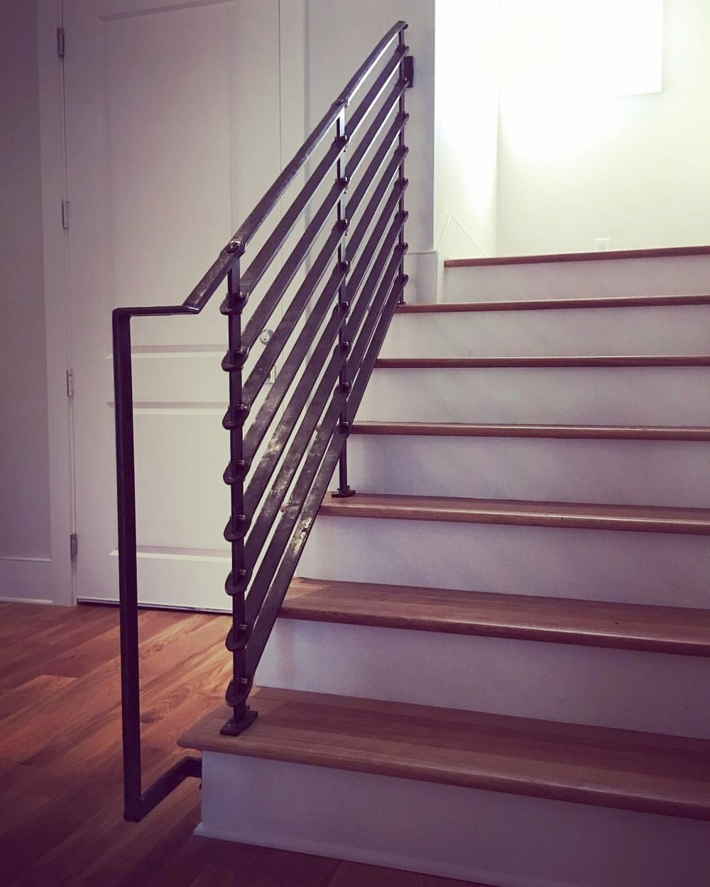 Forged stair railing with brass rivets