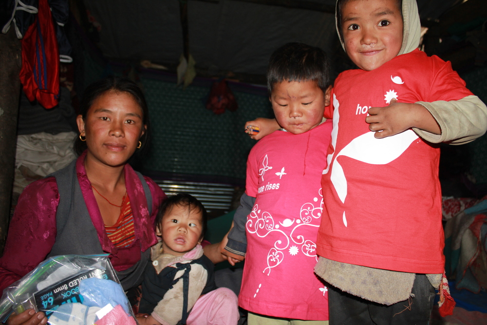 one of the mums receiving a gift package plus her children modelling their t shirts in Gatlang
