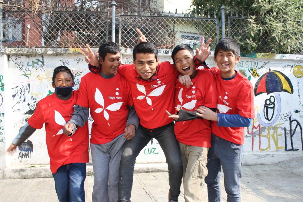 Umbrella boys modelling their Hope Rises Nepal shirts