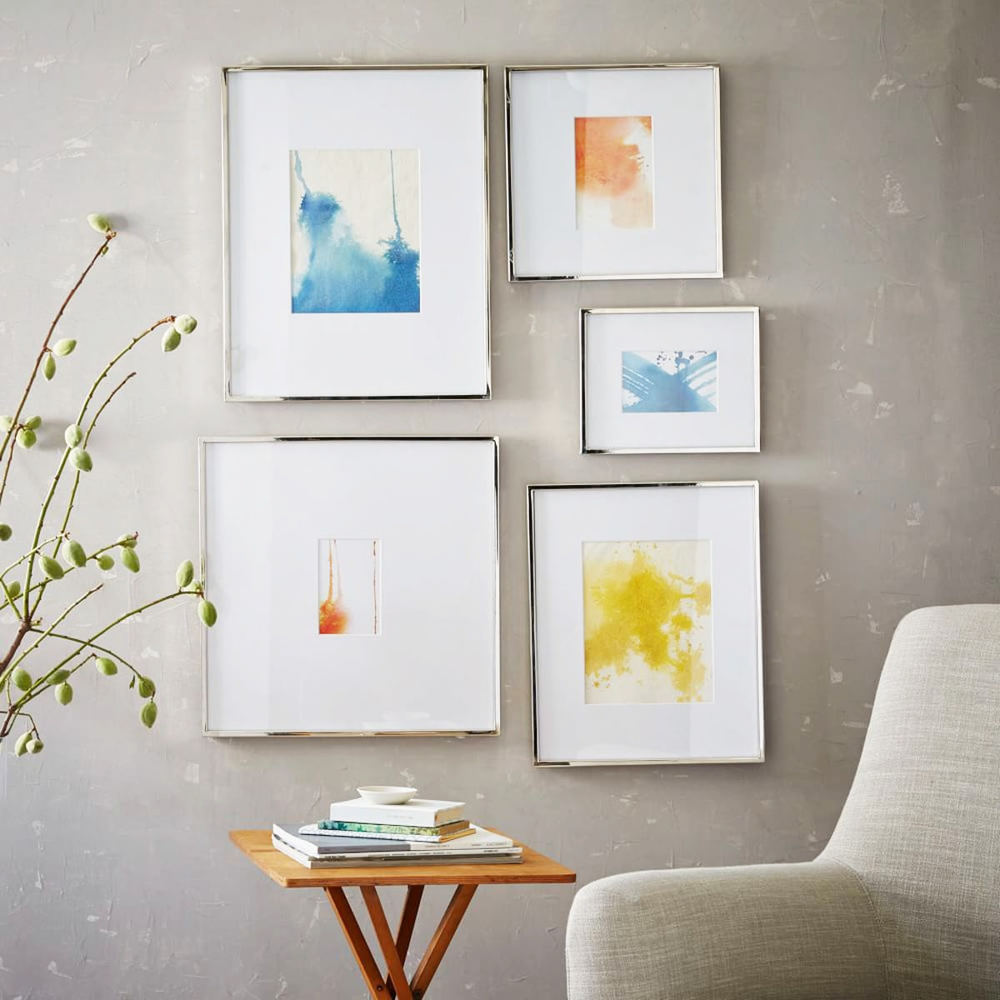 silver  fine art frame collection on concrete wall above chair