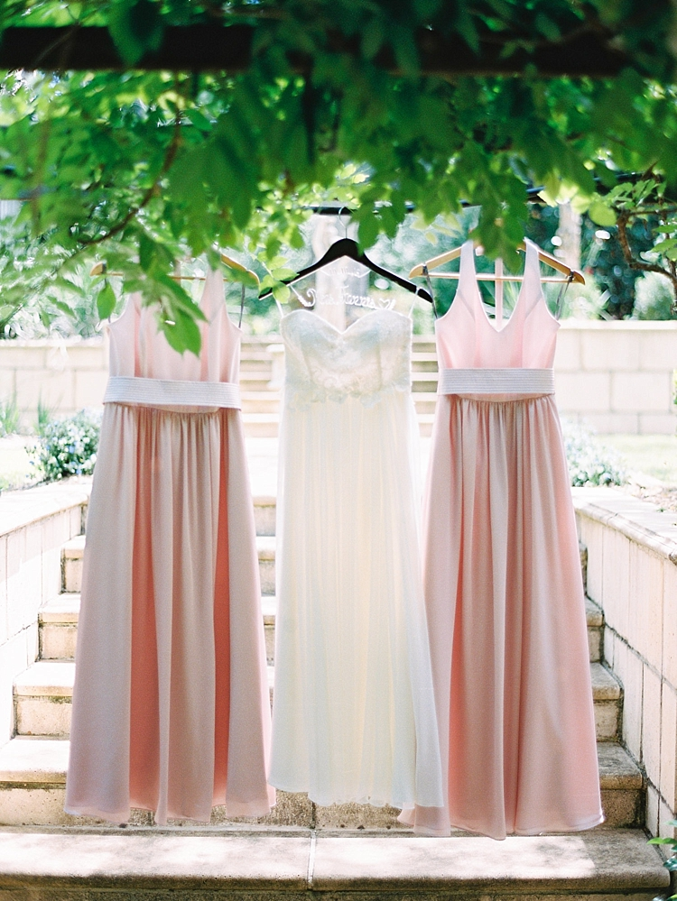 000002 Brisbane Fine Art Wedding Photograph of brides wedding dress and bridesmaids dresses hanging under vines.jpg