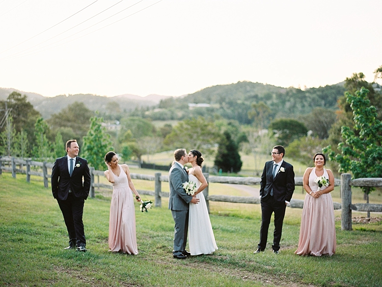 000020 Brisbane Fine Art Wedding Photograph of wedding party in feild while grrom and bride kiss in the middle.jpg