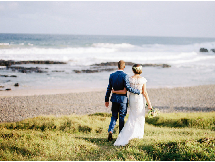 beach-sea-bridal-portrait-bride-byron-bay-nsw-coastal-dress-fine-art-wedding-photographer-grass-groom-hugging-looking-view-walking.jpg