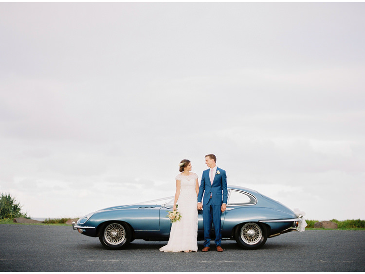 bridal-portrait-bride-byron-bay-nsw-car-coastal-convertable-destination-dress-e-type-fine-art-wedding-photographer-groom-holding-hands-jaguar.jpg