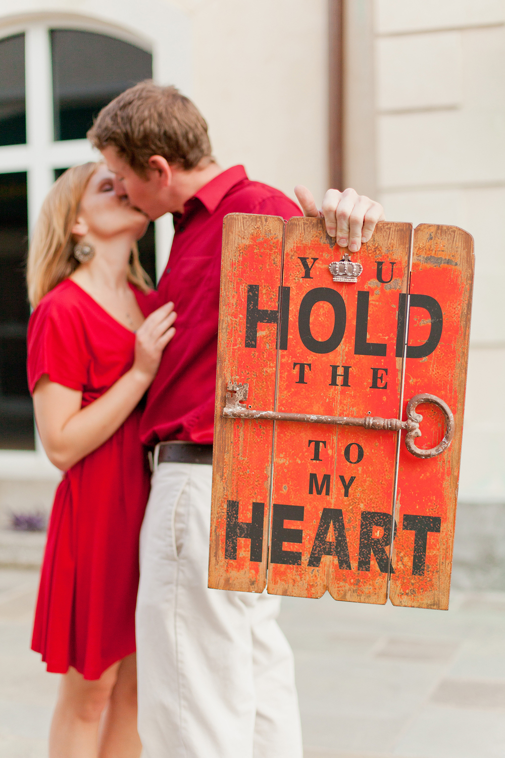 A Couple Kissing while holding a You Hold the Key to my Heart Sign
