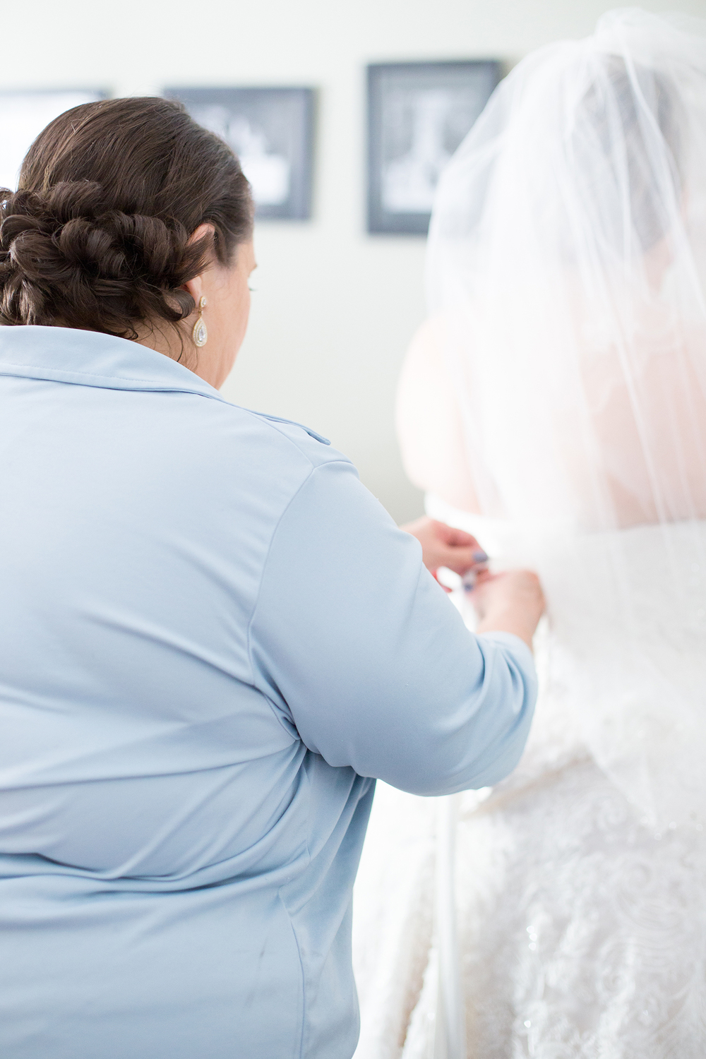 Mom Helping her Daughter into her Wedding Gown