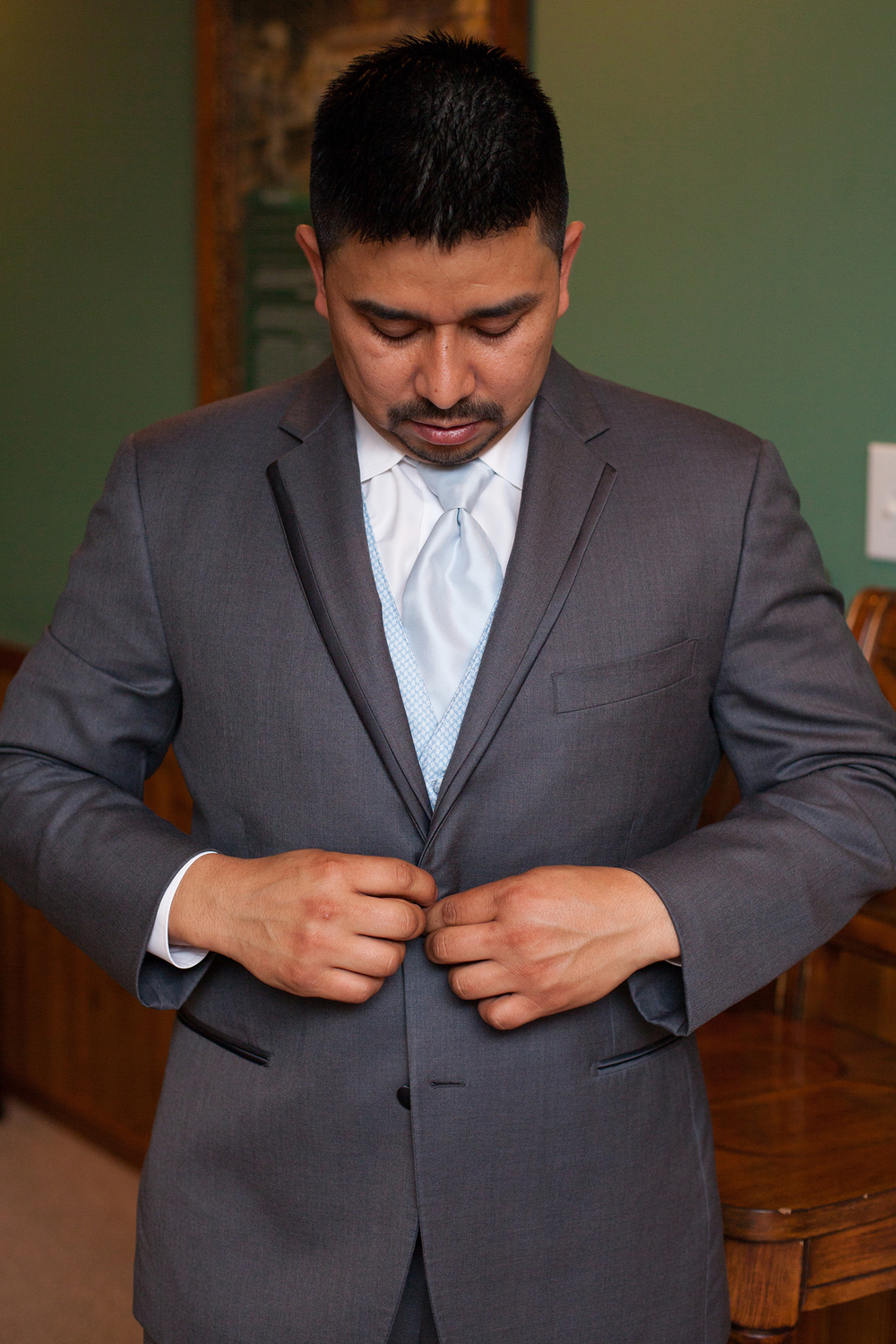 Groom Buttoning his Jacket