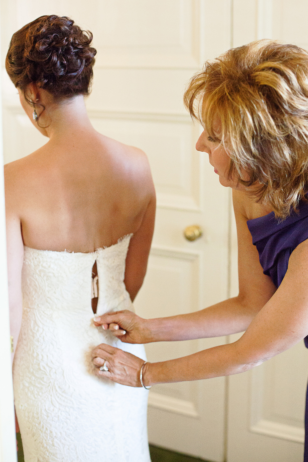 Mother Helping her Daughter into her Wedding Gown