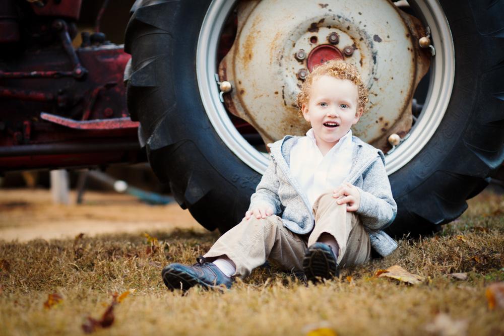 portrait sitting by tractor wheel georgia farm