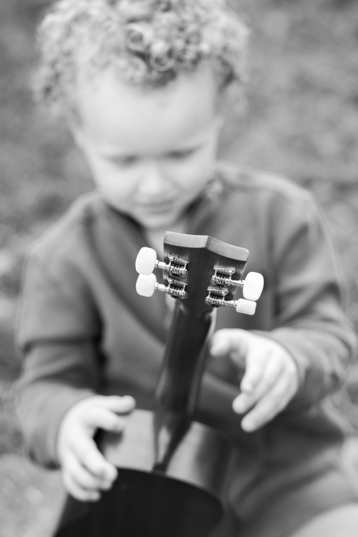 photography of boy playing ukulele