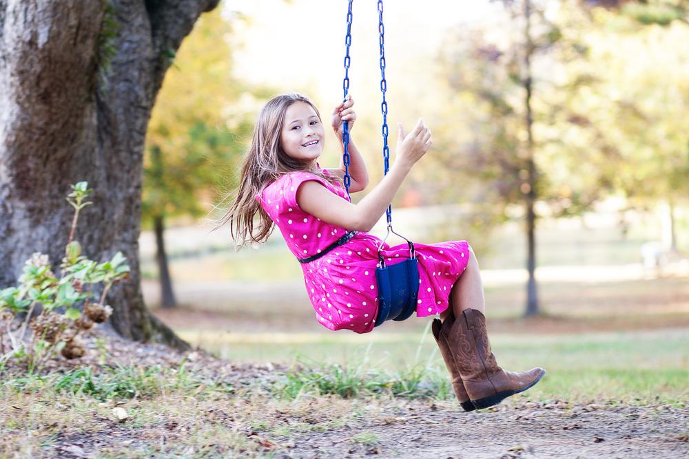 outdoor portrait of girl swinging