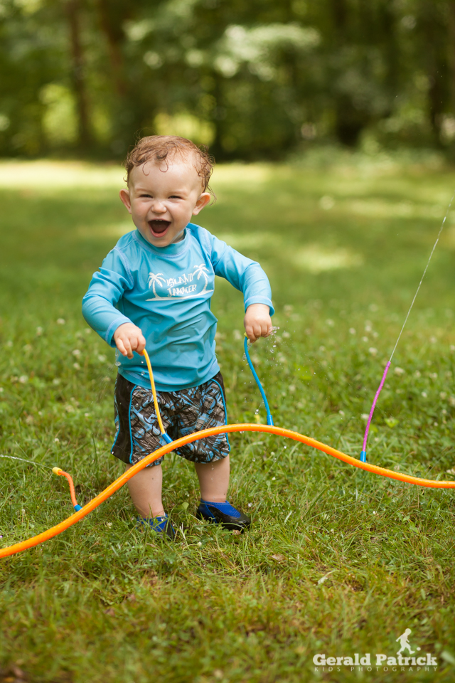 Covington kids photographer boy playing sprinkler