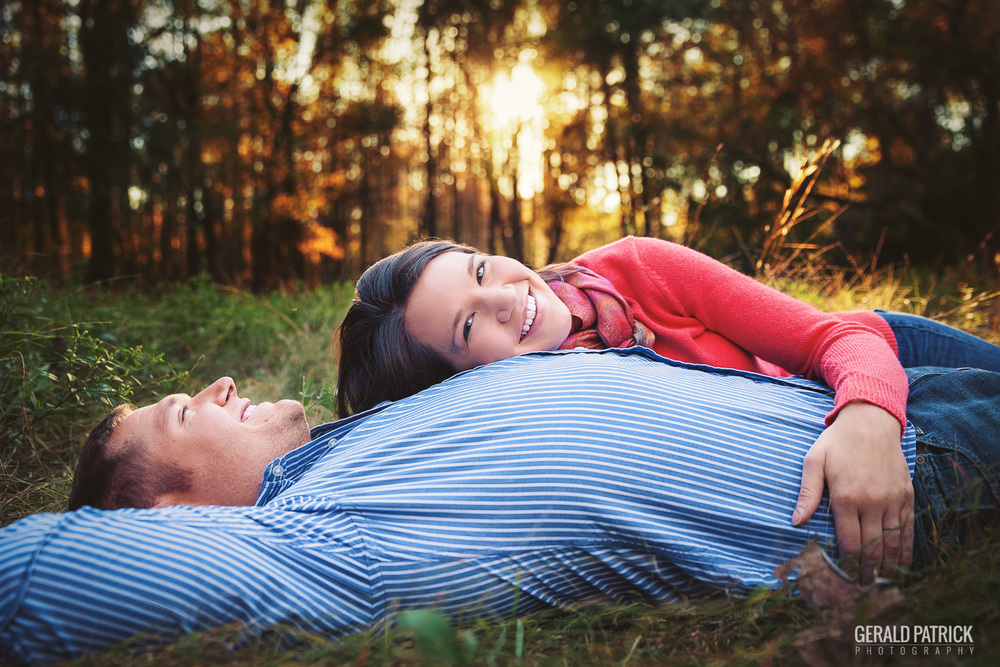 Covington GA photographer engagement lying in meadow at sunset